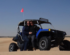 Photo posing with dune buggy at desert